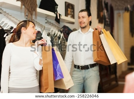 Happy houple with shop-bags at clothing store