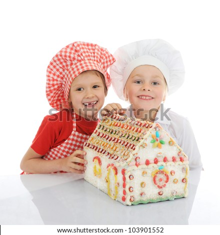 Happy kids cooking gingerbread house - stock photo