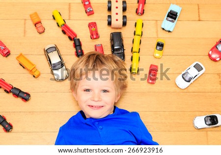 happy little boy playing with toy cars indoor, child fun - stock photo