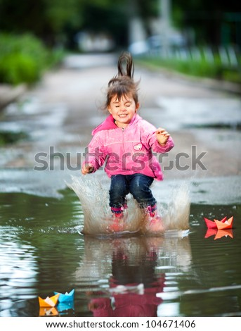 happy little girl, wearing a pink jacket,  jumps into a puddle - stock photo