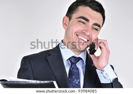 Happy Man. Business man talking on  mobile phone. Pleasant conversation. Isolated on grey - stock photo