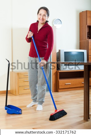 happy mature housewife cleaning with dustpan and brush in living room at home - stock photo