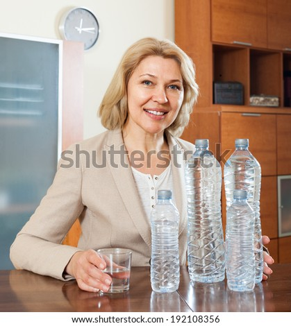Happy mature woman with few bottles of water in home