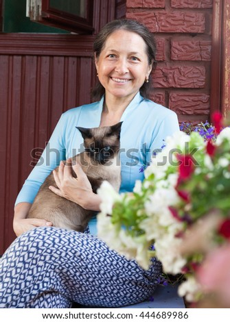 Happy middle-aged woman resting on   porch of   house.