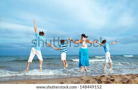 Happy Mother and three sons are jumping on beach
