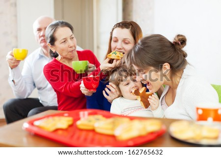 happy multigeneration family communicate over tea with cakes at home interior - stock photo