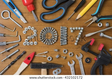 Happy new year 2017 composition with screws, nails,  bolts , dowels and tools on wooden background - stock photo