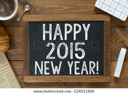 2015 Happy New Year! handwritten with white chalk on a blackboard on a wooden background - stock photo