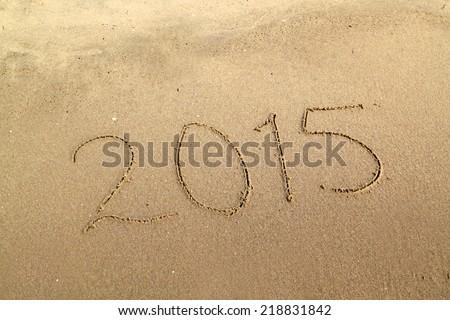 2015 happy new year written on sandy beach - stock photo