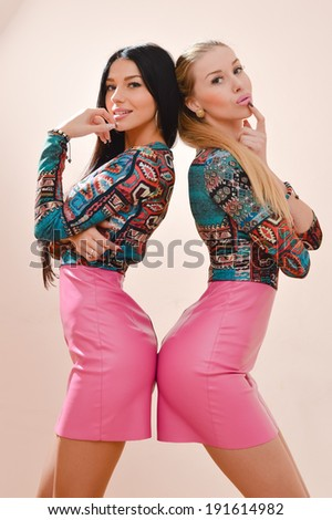 2 happy smiling and looking at camera sisters or best girl friends beautiful blond & brunette young women having fun playfully posing wearing same bright dresses picture on pink background image - stock photo