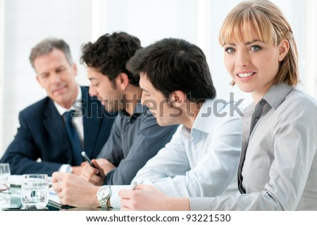 Happy smiling business woman looking at camera with satisfaction at office - stock photo