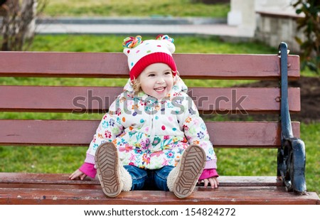 happy toddler girl sitting on the bench outdoor - stock photo