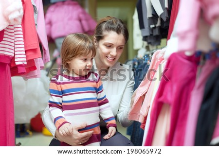 Happy woman and child chooses wear at store - stock photo