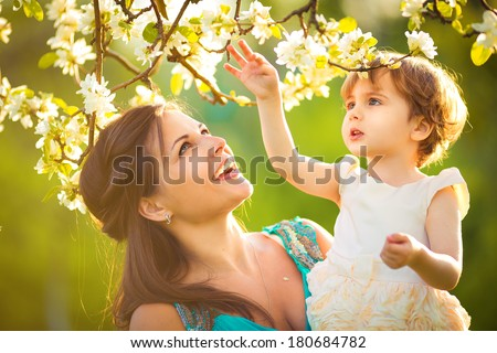 Happy woman and child in the blooming spring garden.Child kissing woman. Mothers day holiday concept - stock photo