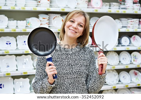 Happy woman housewife chooses frying pan for housekeeping - stock photo
