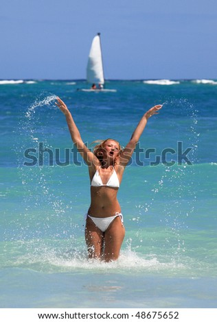 Happy woman playing in water in the caribbean beach,while yacht passing by - stock photo
