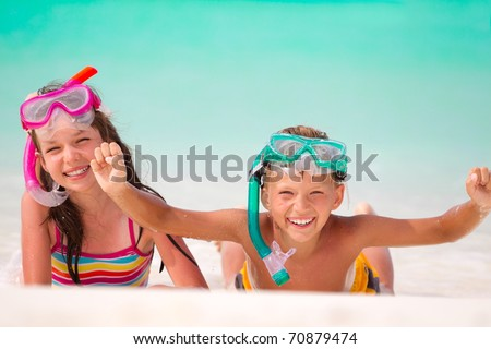 Happy young boy and girl with snorkels on sandy beach, sea in background.
