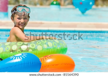 Happy young boy in pool - stock photo