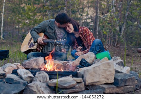 Happy young couple sitting by bonfire - stock photo