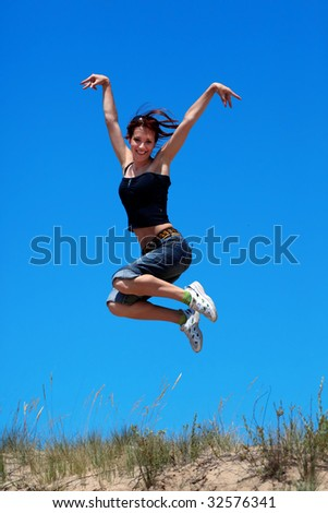 Happy young girl jumping on a background of blue sky