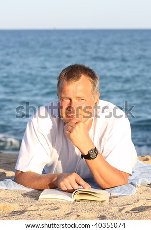 Happy young man reading on the shore - stock photo