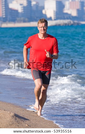 Happy young man running on the beach - stock photo