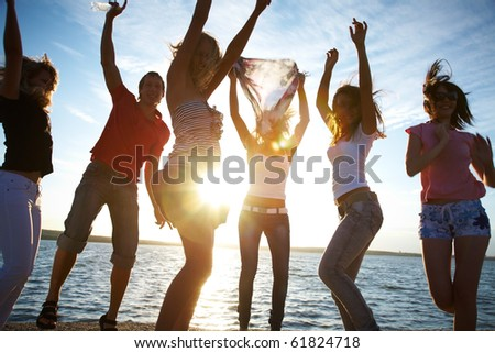 happy young people are  dancing at the beach on  beautiful summer sunset - stock photo