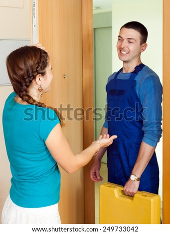 Happy young  workman  came to call the housewife - stock photo