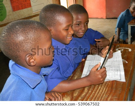 Harare,Zimbabwe,January 16 2016 Three smiling  primary  school boys in  blue school  using  a cellphone tablet  in  a  classroom.