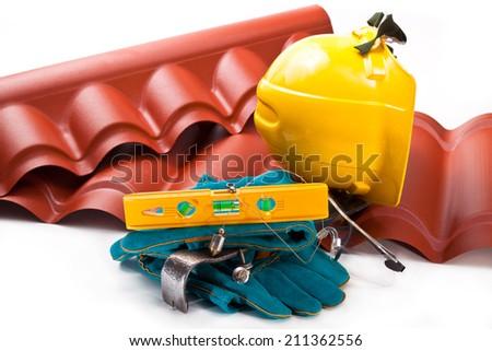 Hardhat,  roof , mount, level, gloves, screws - stock photo