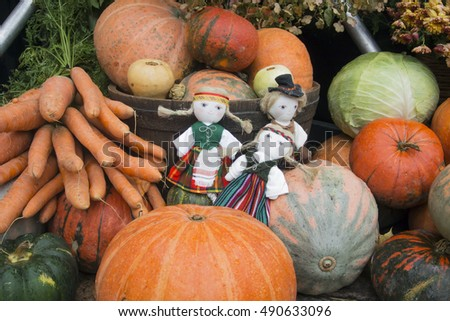 Harvest holiday, Halloween.  Dolls in national suits among pumpkins.