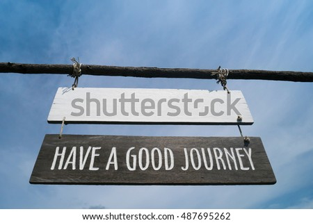 'Have a good journey' Wooden sign board hanging on wooden pole with blue sky as background