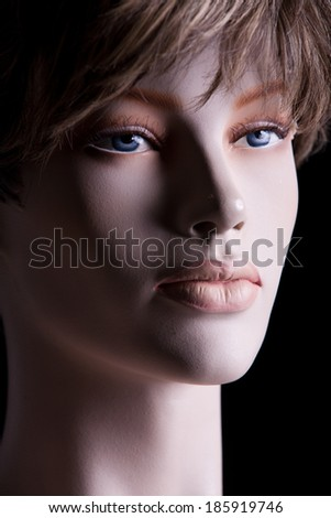 head of the female dummy in bright wig on a black background - stock photo