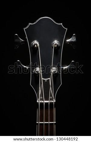 Head stock of a dark electrical bass guitar - stock photo
