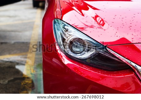 headlights of red car after the rain on street - stock photo
