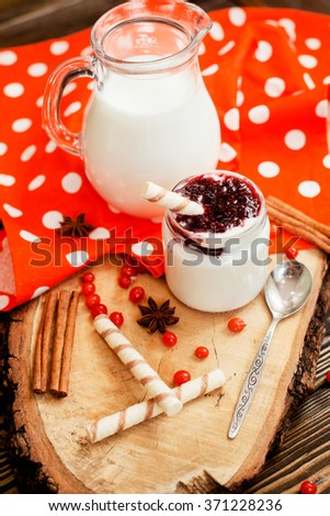 healthy breakfast , pudding or yogurt with strawberry and cherry jam , milk , sweet tubes , berries and cinnamon on a wooden background