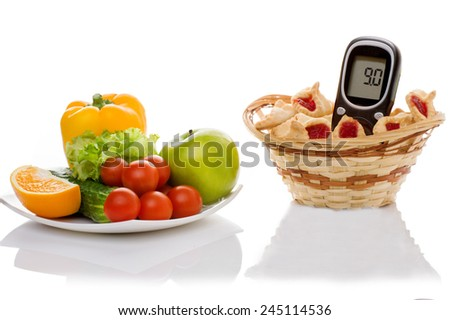 healthy organic food and cookies with glucometer on a white background