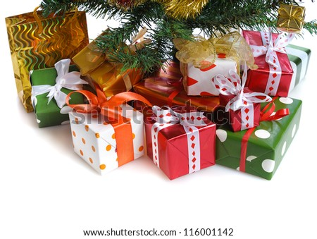 heap of  red  gift boxes  with satin bow  under decorated Christmas tree - stock photo