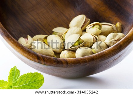 heap salted pistachio nuts in wooden bowl background - stock photo
