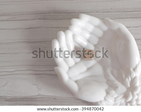 """""""heart"""" printed on a wooden block inside two hands greeting card design - stock photo"""