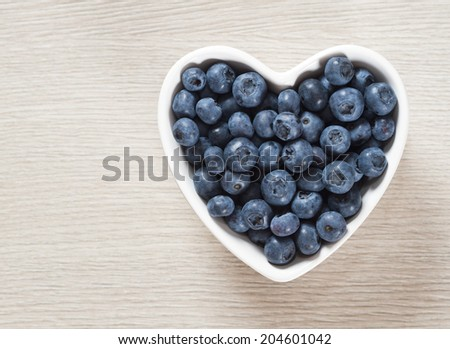 Heart shaped bowl of blueberries on  wooden table - stock photo