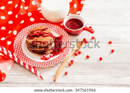 hearty breakfast, sweet American pancakes with raspberry , cherry or strawberry jam , berries and milk on a wooden background - stock photo