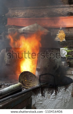 Heat in ancient metal crucible , Ancient metal cast for buddha statue  in Lok Molee Temple, Chiangmai, Thailand. - stock photo