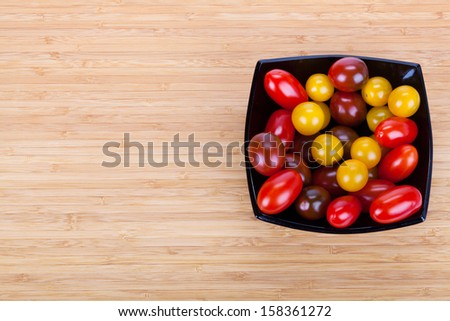 ��¡herry tomatoes in black plate on wooden table with slices of green pepper - stock photo