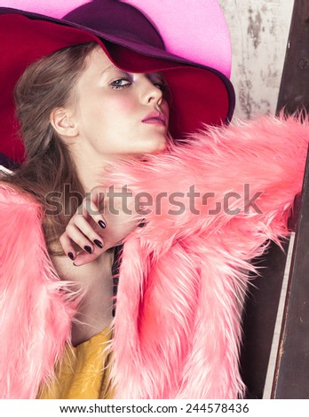 High fashion portrait of young girl in pink hat and fur coat at the white wall with wooden ladder - stock photo