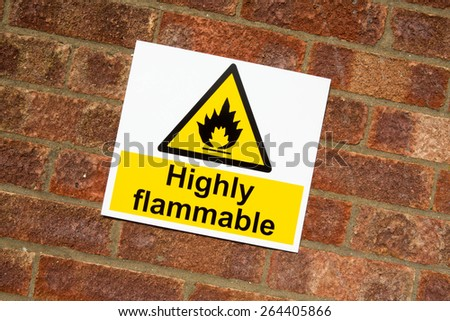 """""""Highly Flammable """" danger sign on a brick wall background - stock photo"""