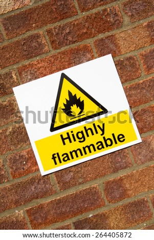 """Highly Flammable "" danger sign on a brick wall background - stock photo"