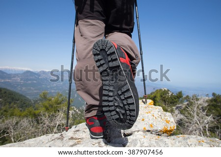 Hiker standing on top of the mountain with valley on the background. - stock photo