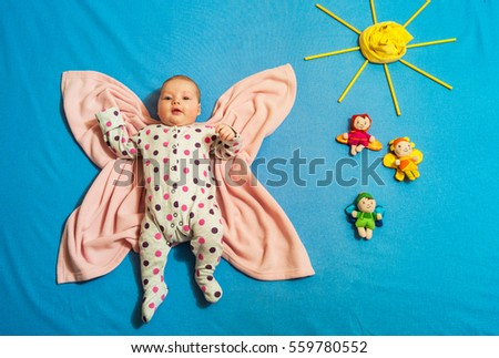 �¡hild dressed in a Catsuit lying on a towel on the bed in the form of a butterfly