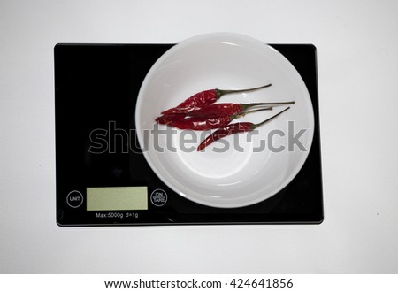 Ð¡hili peppers on a digital white kitchen scale. (weighing products) - stock photo